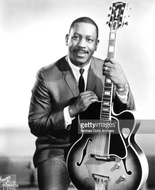 Jazz guitarist Wes Montgomery poses for a portrait holding a Gibson hollow body electric guitar during his sting on Verve Records in 1965