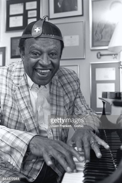 Jazz musician Lionel Hampton plays the piano in his New York home