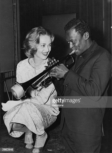 Jazz musician Miles Davis playing his horn with French actress Jeanne Moreau watching admiringly