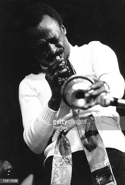 Jazz musician Miles Davis plays his trumpet onstage in circa 1975