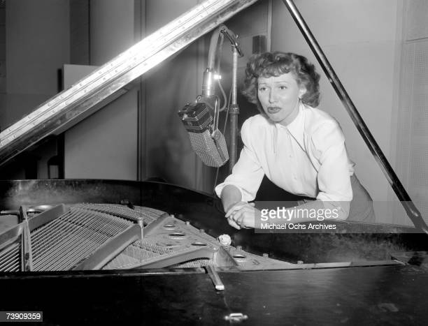 Jazz singer Anita O'Day leans on the piano in the studio at Capitol Records on February 18 1947 in Los Angeles California