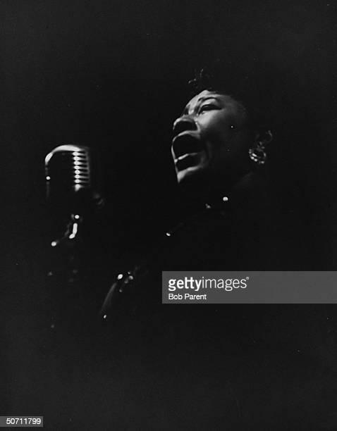 Jazz singer Ella Fitzgerald singing in front of mike in darkened setting