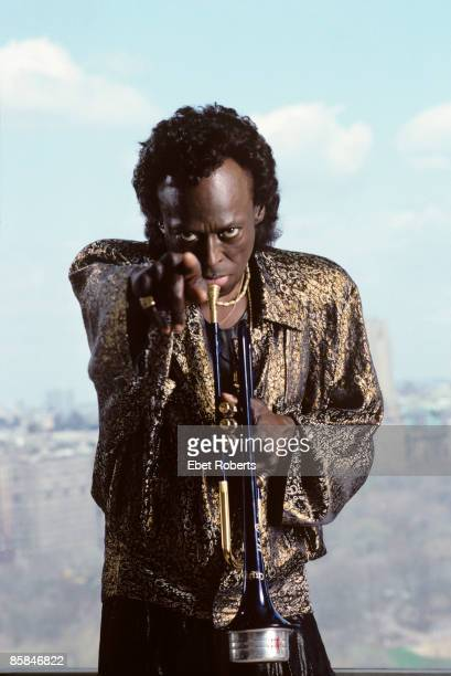 Photo of Miles DAVIS posed studio holding trumpet pointing to camera