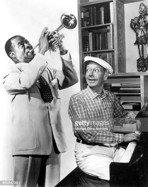 Jazz trumpeter singer and actor Louis Armstrong rehearses on the set of the movie 'High Society' with composer Cole Porter in 1956 in Los Angeles...
