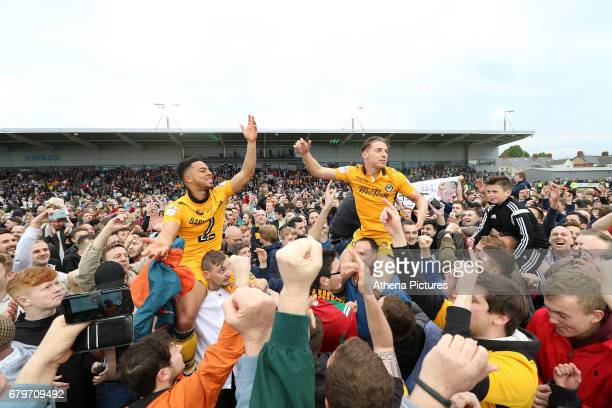 Jazzi BarnumBobb of Newport County and Sid Nelson celebrates with fans during a pitch invasion after the final whistle as a late goal from Mark...