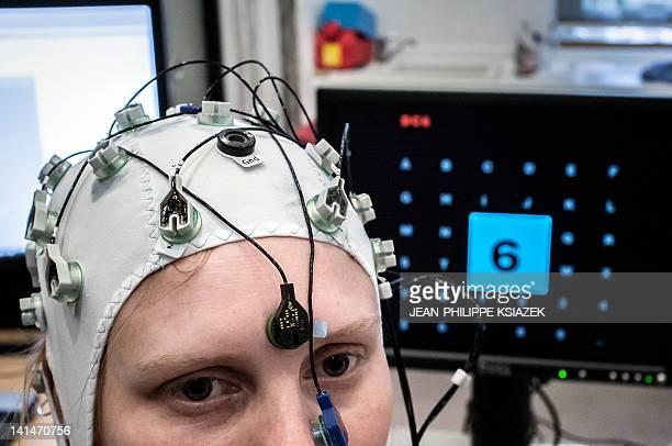 REBOUL 'Je pense donc j'écris' formule mise en musique par des neuroscientifiques' A test person wearing a cap with electrodes poses at the...