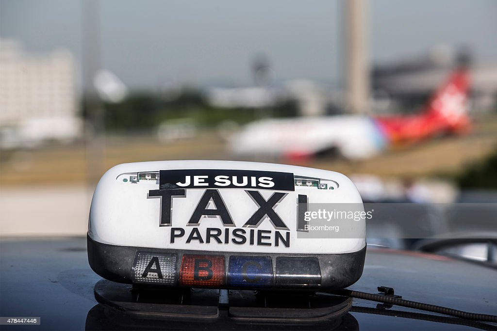 A Je Suis Taxi sign sits on a rooftop hire sign of a cab outside Charles de Gaulle airport during a protest against Uber Technologies Inc.'s car sharing service in Roissy, France, on Thursday, June 25, 2015. French taxi drivers are on indefinite nationwide strike as they demand a government crackdown on what they say is Uber's use of unlicensed chauffeurs for its UberPop service. Photographer Balint Porneczi/Bloomberg via Getty Images