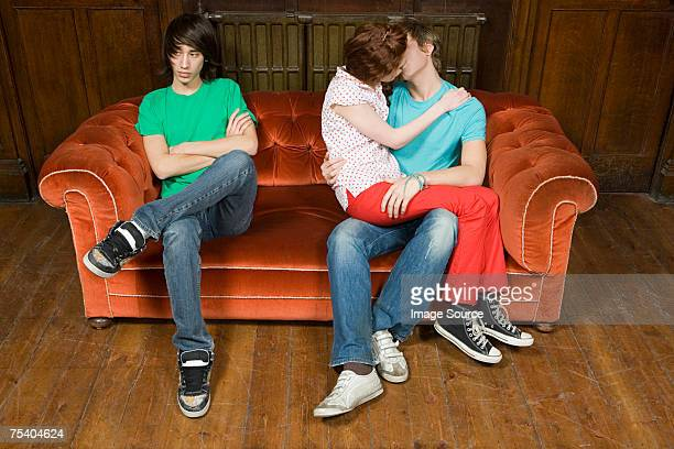 Jealous teenager with kissing couple