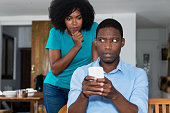 Jealousy african american woman checking chat on cellphone of boyfriend at home