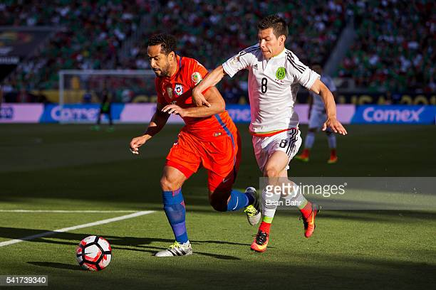 Jean Beausejour of Chile fights for the ball with Hirving Lozano of Mexico during a Quarterfinal match between Mexico and Chile at Levi's Stadium as...