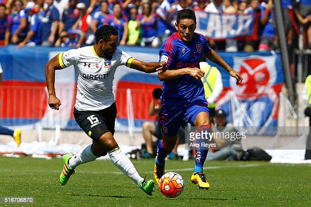 Jean Beausejour of Colo Colo fights for the ball with Matias Rodriguez of U de Chile during a match between U de Chile and Colo Colo as part of...