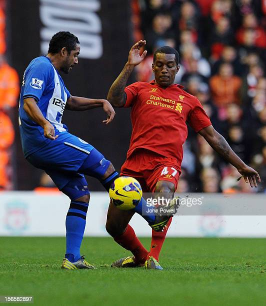 Jean Beausejour of Wigan and Andre Wisdom of Liverpool compete during the Barclays Premier League match between Liverpool and Wigan Athletic at...