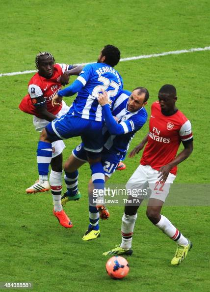 Jean Beausejour of Wigan Athletic clashes with teammate Ivan Ramis of Wigan Athletic as Yaya Sanogo of Arsenal controls the ball during the FA Cup...