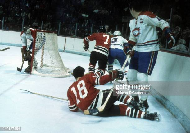 Jean Beliveau and goalie Ken Dryden of the Montreal Canadiens and Gerry Pinder of the Chicago Blackhawks look on as JC Tremblay of the Canadiens and...
