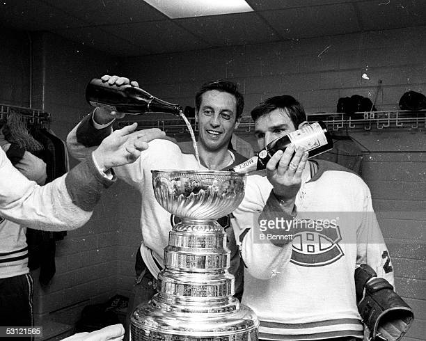 Jean Beliveau and teammate John Ferguson of the Montreal Canadiens fill up the Stanley Cup Trophy with champagne in the locker room after defeating...