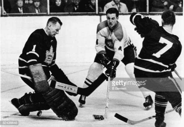 Jean Beliveau of the Montreal Canadiens flicks the puck between the legs of goalie Johnny Bower of the Toronto Maple Leafs while Bower's teammate Tim...
