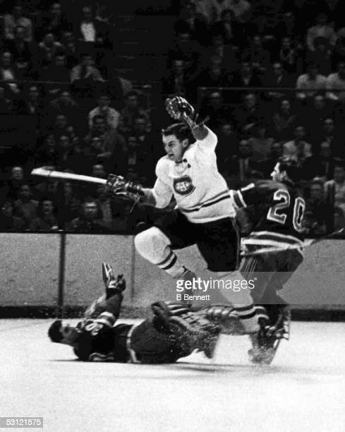 Jean Beliveau of the Montreal Canadiens leaps over goalie Cesare Maniago of the New York Rangers as his teammate Phil Goyette defends circa 1966 at...