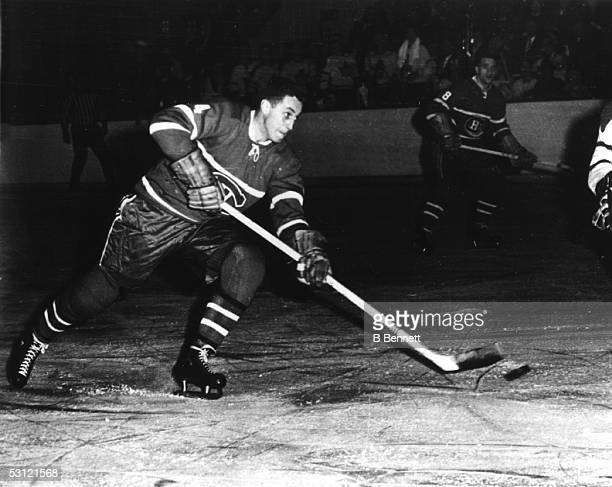 Jean Beliveau of the Montreal Canadiens passes the puck during Game 2 of the 1960 Stanley Cup Finals on April 9 1960 at the Montreal Forum in...