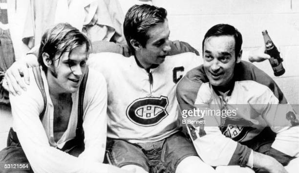 Jean Beliveau of the Montreal Canadiens puts his arms around teammates goalie Ken Dryden and Frank Mahovlich following their victory over the Chicago...