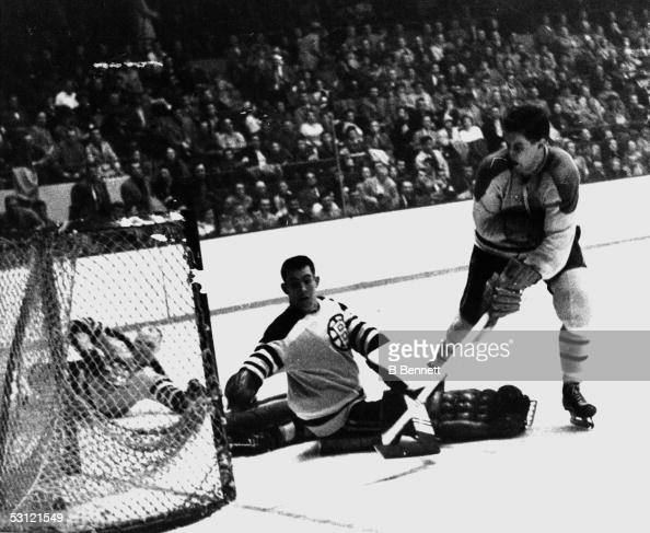 Jean Beliveau of the Montreal Canadiens scores on goalie Don Simmons of the Boston Bruins on March 3 1957 at the Boston Garden in Boston Massachusetts