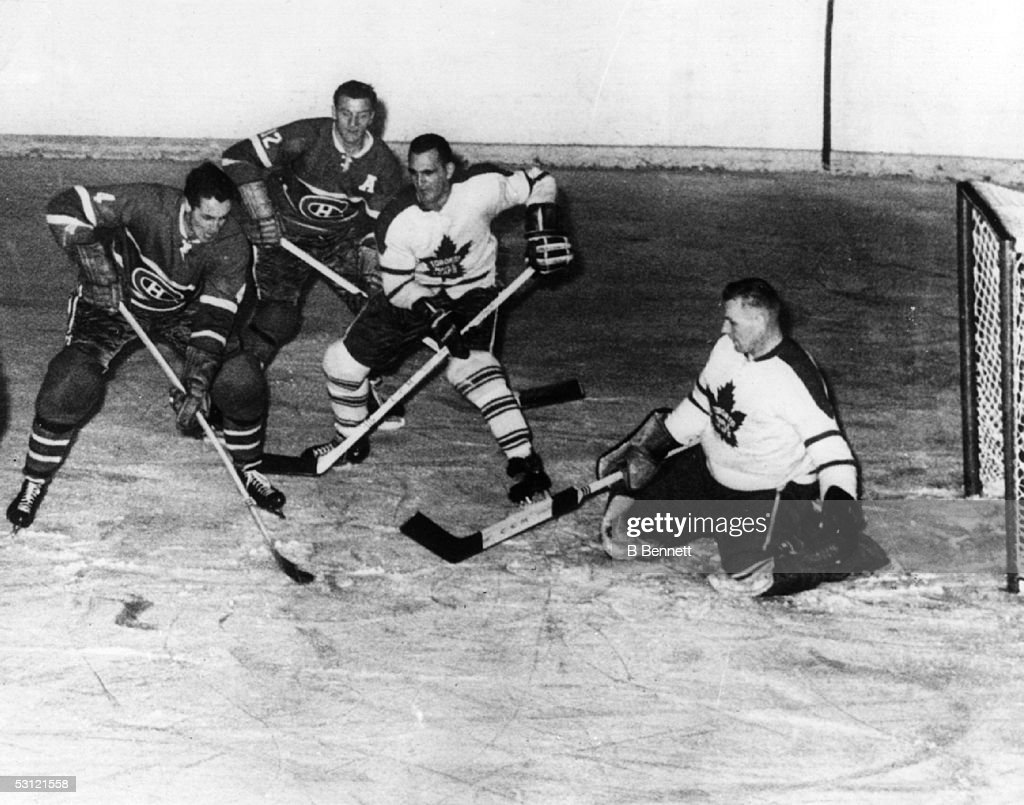 Jean Beliveau #4 of the Montreal Canadiens scores on goalie <a gi-track='captionPersonalityLinkClicked' href=/galleries/search?phrase=Johnny+Bower&family=editorial&specificpeople=239053 ng-click='$event.stopPropagation()'>Johnny Bower</a> #1 of the Toronto Maple Leafs on November 3, 1960 at the Montreal Forum in Montreal, Quebec, Canada.