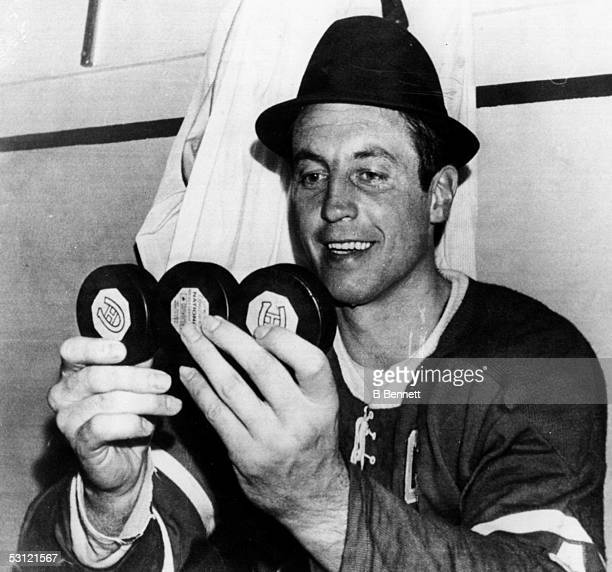 Jean Beliveau of the Montreal Canadiens sits in the locker room while holding the three pucks that he scored his hat trick during Game 2 of the 1968...