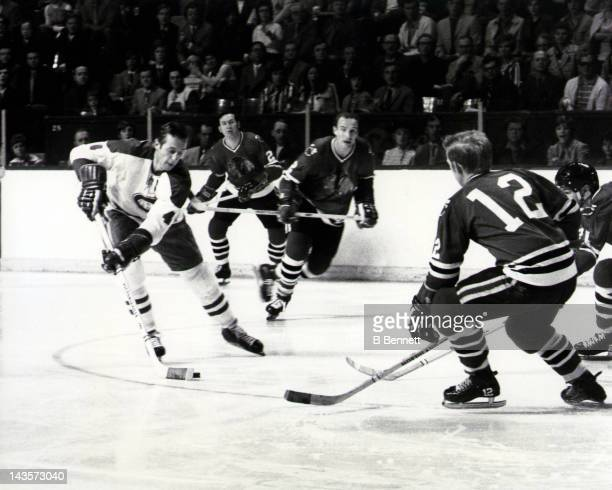 Jean Beliveau of the Montreal Canadiens skates with the puck as Bill White Pat Stapleton and Stan Mikita of the Chicago Blackhawks defend during a...