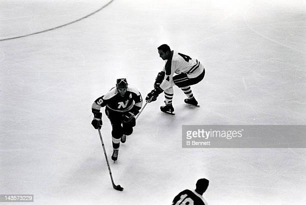 Jean Beliveau of the Montreal Canadiens tries to hook Charlie Burns of the Minnesota North Stars during their game circa 1971 at the Montreal Forum...