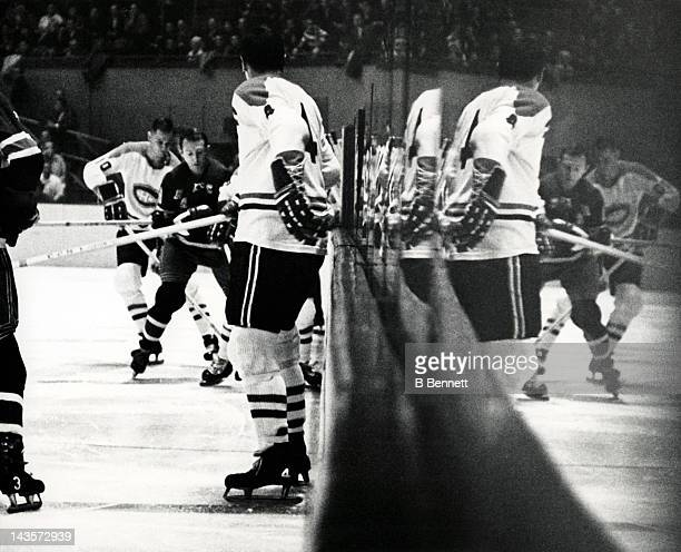 Jean Beliveau of the Montreal Canadiens waits along the boards as he watches his teammate Ted Harris and Bob Nevin of the New York Rangers battle for...