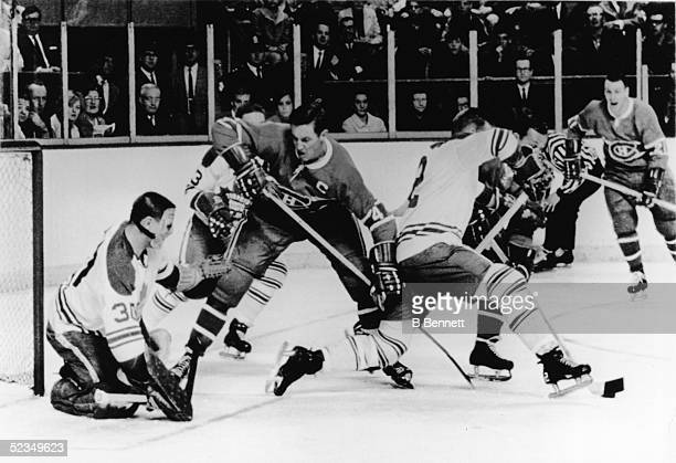 Jean Beliveu of the Montreal Canadiens moves in on goalie Terry Sawchuk of the Toronto Maple Leafs as Larry Hillman of the Maple Leafs steals the...