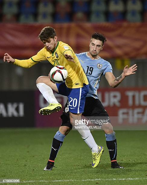 Jean Carlos of Brazil takes a pass with Erick Cabaco of Uruguay during the FIFA Under20 World Cup football round of 16 match between Brazil and...
