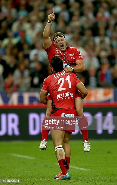 Jean Charles Orioli of Toulon is picked up by his jubilant team mate Maime Mermoz of Toulon after Toulon wins the Top 14 Final between Toulon and...