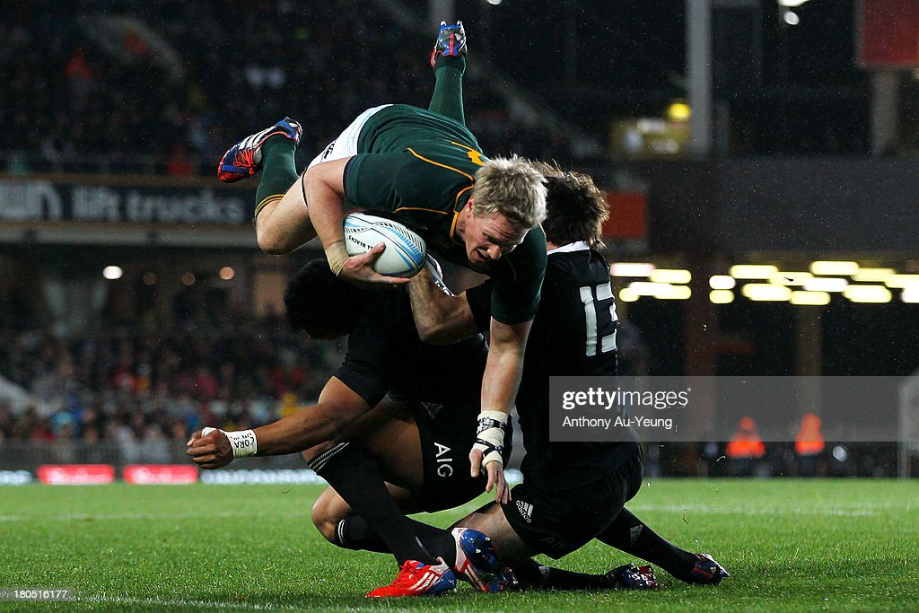 <a gi-track='captionPersonalityLinkClicked' href=/galleries/search?phrase=Jean+de+Villiers&family=editorial&specificpeople=2285701 ng-click='$event.stopPropagation()'>Jean de Villiers</a> of South Africa charges over <a gi-track='captionPersonalityLinkClicked' href=/galleries/search?phrase=Julian+Savea&family=editorial&specificpeople=5780264 ng-click='$event.stopPropagation()'>Julian Savea</a> and <a gi-track='captionPersonalityLinkClicked' href=/galleries/search?phrase=Conrad+Smith&family=editorial&specificpeople=644500 ng-click='$event.stopPropagation()'>Conrad Smith</a> of New Zealand during The Rugby Championship match between the New Zealand All Blacks and the South African Springboks at Eden Park on September 14, 2013 in Auckland, New Zealand.