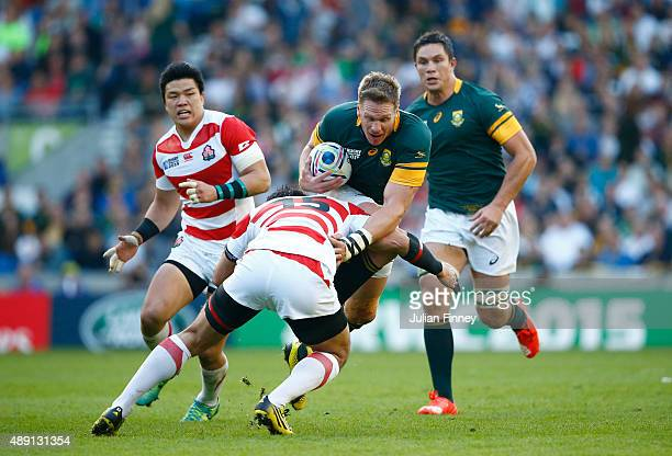 Jean De Villiers of South Africa is tackled by Ayumu Goromaru of Japan during the 2015 Rugby World Cup Pool B match between South Africa and Japan at...