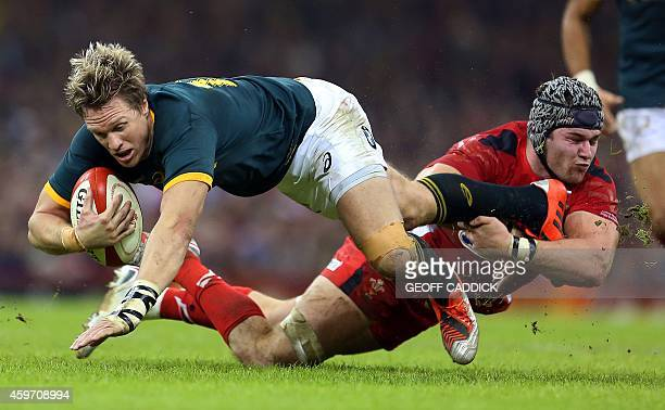 Jean de Villiers of South Africa is tackled by Dan Lydiate of Wales during the Autumn International rugby union Test match between Wales and South...