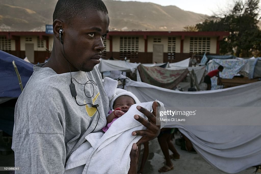 Jean Derosier, holds his baby in a temporary camp where Save the Children is running a' Child Friendly Space' a safe area for children to play in and a mobile clinic on January 30, 2010 in Port Au Prince, Haiti. Jean's wife, Enide gave birth to her first baby, Jean Erik Veillard on January 21st. She is camping in a park near the National Theatre with her husband. As many as 200,000 people died on January 12 as a consequence of the 7.0-magnitude earthquake. At least 130 people have been pulled alive from the rubble. An estimated 1.5 million people have been left homeless. The Haitian government is planning to relocate some 400,000 people, currently in makeshift camps across the capital, to temporary tent villages outside the city. Aid agencies are still struggling to supply food and water to survivors, while thousands of Haitians who suffered serious injuries remain in need of urgent medical attention.