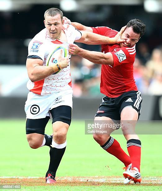 Jean Deysel of the Cell C Sharks hands off Ryan Crotty of the Crusaders during the Super Rugby match between Cell C Sharks and Crusaders at...