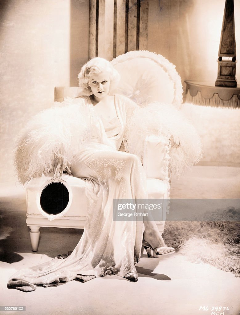 <a gi-track='captionPersonalityLinkClicked' href=/galleries/search?phrase=Jean+Harlow&family=editorial&specificpeople=70012 ng-click='$event.stopPropagation()'>Jean Harlow</a>, in a sequin and feather dressing gown and holding a mirror, lounges seductively on a large white chair. MGM publicity handout.