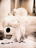 Jean Harlow in a sequin and feather dressing gown and holding a mirror lounges seductively on a large white chair MGM publicity handout