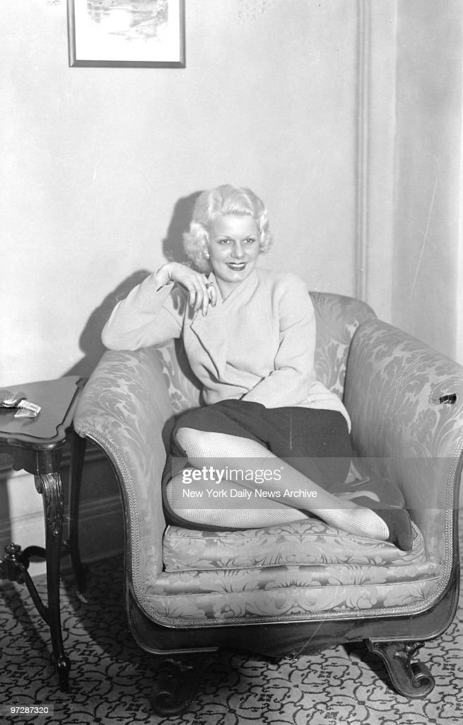 Jean Harlow, the screen's original platinum blonde, refreshed and rested after the long trip, exudes fascination as she lolls in a soft chair at her hotel.