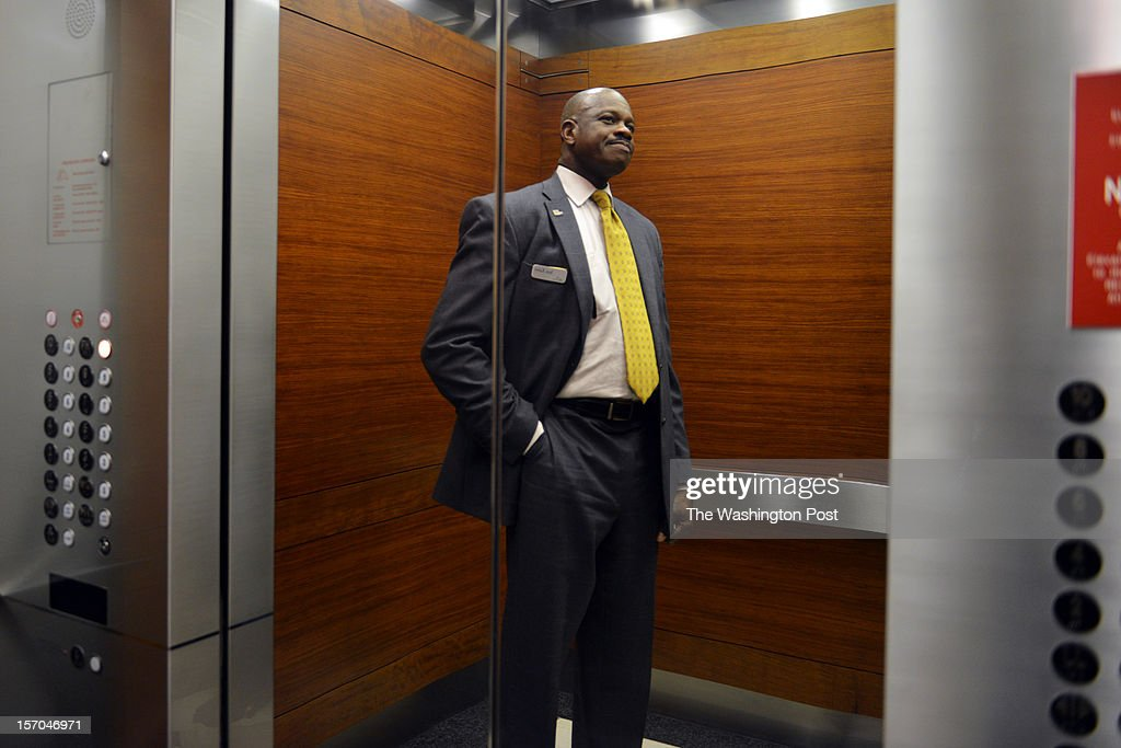 Jean Kabre takes an elevator to the floor of his office where he works as a concierge and event planner at 101 Constitution Avenue on Tuesday, November 13, 2012, in Washington, DC. Kabre is the charismatic, always-smiling guy who has befriended the entire building. So much so that, as people watched him drain his paycheck every week to keep dozens of relatives in Burkina Faso from starving, they decided to pitch in. Starting with a pump to replace the village's muddy drinking-water hole, they now have an ambitious plan to feed, house, educate and equip the people of Tintilou to start their own business grinding grain. At a time when many established charities have massive operations and overhead expenses, and in a city where the desire to help often gets mired in politics and bureaucracy, the ability to give directly to a friend just felt more natural than sending off another check.