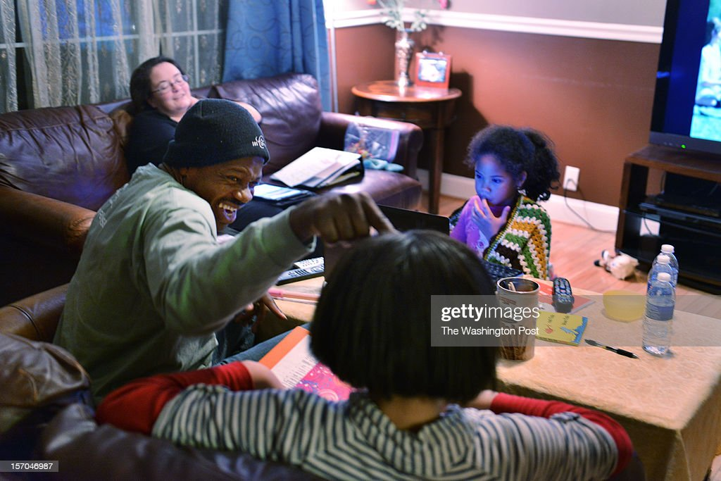 Jean Kabre teases with his daughter, Timbila Kabre, 15, as they discuss homework at the Kabre home on Thursday, November 13, 2012, in Woodbridge, VA. Jean's wife Susan, back left, and daughter Wendlassida Kabre, 7, back right, sit by. Jean Kabre is the charismatic, always-smiling guy who has befriended the entire building where he works at 101 Constitution Avenue. So much so that, as people watched him drain his paycheck every week to keep dozens of relatives in Burkina Faso from starving, they decided to pitch in. Starting with a pump to replace the village's muddy drinking-water hole, they now have an ambitious plan to feed, house, educate and equip the people of Tintilou to start their own business grinding grain. At a time when many established charities have massive operations and overhead expenses, and in a city where the desire to help often gets mired in politics and bureaucracy, the ability to give directly to a friend just felt more natural than sending off another check.