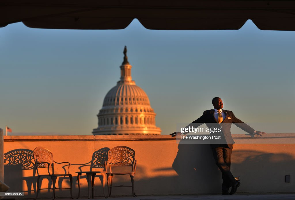 Jean Kabre watches the development of D.C. from the rooftop of the building where he works as a concierge and event planner at 101 Constitution Avenue on Tuesday, November 13, 2012, in Washington, DC. Kabre is the charismatic, always-smiling guy who has befriended the entire building. So much so that, as people watched him drain his paycheck every week to keep dozens of relatives in Burkina Faso from starving, they decided to pitch in. Starting with a pump to replace the village's muddy drinking-water hole, they now have an ambitious plan to feed, house, educate and equip the people of Tintilou to start their own business grinding grain. At a time when many established charities have massive operations and overhead expenses, and in a city where the desire to help often gets mired in politics and bureaucracy, the ability to give directly to a friend just felt more natural than sending off another check.