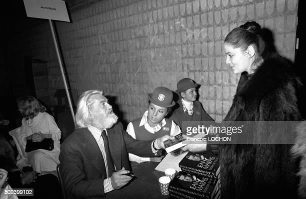 Jean Marais dédicace ses ouvrages lors de la vente annuelle de livres au Pen Club le 2 décembre 1978 à Paris France