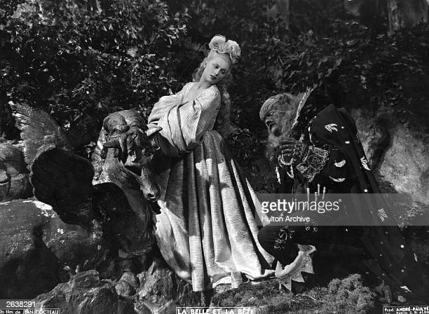 Jean Marais kneels at the feet of Josette Day in a scene from Jean Cocteau's beautifully surreal film 'La Belle Et La Bete' based on the children's...