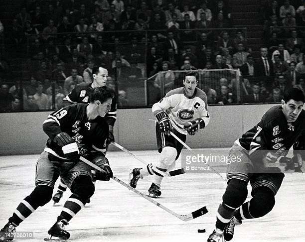 Jean Ratelle of the New York Rangers skates with the puck as Jean Beliveau of the Montreal Canadiens follows behind during their game on October 24...