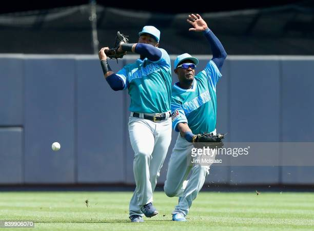 Jean Segura and Guillermo Heredia of the Seattle Mariners can't come up with a ball hit by Gary Sanchez of the New York Yankees during the first...