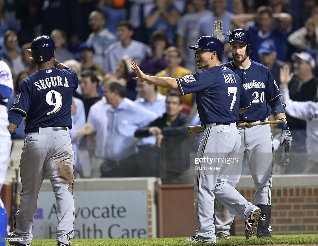 <a gi-track='captionPersonalityLinkClicked' href=/galleries/search?phrase=Jean+Segura&family=editorial&specificpeople=7521808 ng-click='$event.stopPropagation()'>Jean Segura</a> #9 (L-R), <a gi-track='captionPersonalityLinkClicked' href=/galleries/search?phrase=Norichika+Aoki&family=editorial&specificpeople=850957 ng-click='$event.stopPropagation()'>Norichika Aoki</a> #7 and <a gi-track='captionPersonalityLinkClicked' href=/galleries/search?phrase=Jonathan+Lucroy&family=editorial&specificpeople=5732413 ng-click='$event.stopPropagation()'>Jonathan Lucroy</a> #20 of the Milwaukee Brewers celebrate after Segura and Aoki scored on an RBI single hit by teammate Jeff Bianchi #14 during the ninth inning against the Chicago Cubs of game two of a double header at Wrigley Field on July 30, 2013 in Chicago, Illinois. The Brewers defeated the Cubs 3-2.