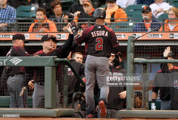 Jean Segura of the Arizona Diamondbacks is congratulated by manager Chip Hale after Segura hit a lead off solo home run against the San Francisco...