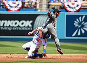 Jean Segura of the Arizona Diamondbacks jumps over Enrique Hernandez of the Los Angeles Dodgers after getting the force out at second in the first...